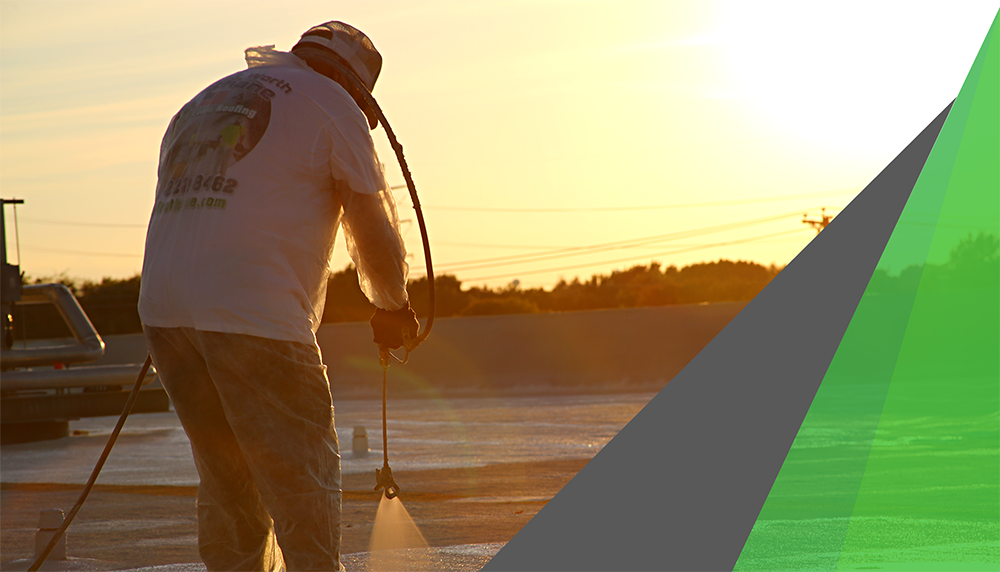 A man in a white T shirt is photographed against the sunset as he applies spray foam to a commercial roof. Spray foam works well as insulation against heat loss.