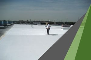 A man in a white T shirt applies spray foam to a commercial roof. Spray foam also is used for building insulation, providing superior R value compared to traditional insulation.