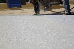 Closed cell spray foam used as commercial roof system is being applied by a professional roofing company