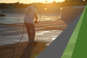 A man spraying polyurethane foam, the best insulation to reduce utility bills, onto the roof of a commercial building. The sun is setting in the background.