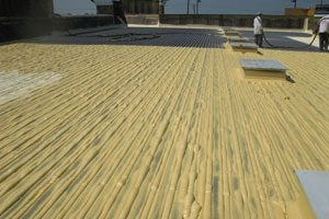 A commercial roof which is mid-way through the installation of a new tan-colored SPF roofing system, which contains the best insulation to reduce utility bills.
