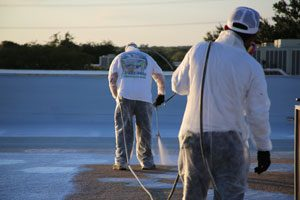 Two men in long-sleeved white shirts applying a white spray polyurethane liquid, the best insulation to reduce utility bills, onto a commercial roof.