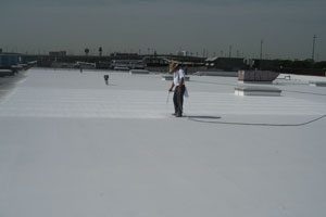 A worker in a long-sleeved white shirt is applying SPF, the best insulation to reduce utility bills, onto the roof of a very large commercial building.