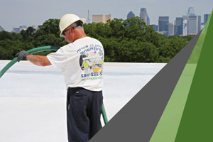 A roofing worker in a white t-shirt and white hard hat examines a commercial roof, pondering the reflective roof options he could employ.