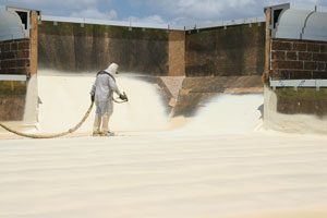 A worker wearing protective gear is applying a reflective roof coating with a spray gun to a commercial roof.