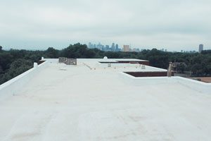 A large commercial roof that has been covered in white reflective roof coating.