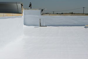 Pictured is a corner section of a commercial roof that has been covered in a white reflective roof coating.