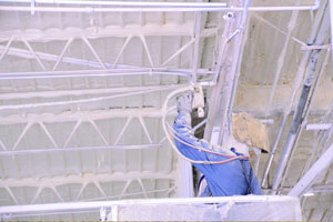 A man wearing blue protective clothing applies SPF insulation to an industrial building's ceiling. SPF is also used to insulate industrial walk-in freezers.