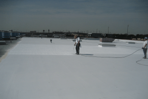 A worker wearing protective clothing sprays on an elastomeric coating for TPO onto a large commercial roof.