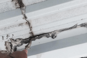 The picture shows a crack between panels of a TPO roof, which could be resolved by applying an elastomeric coating.