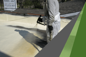 A worker wearing gray protective clothing sprays on an elastomeric roof coating, which protects roofs from severe weather damage.