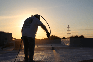 A worker is silhouetted against the sunset as he applies a roof coating to a commercial roof. These coatings protect against severe weather common to North Texas.