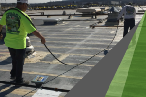 A worker in a neon green t-shirt applies an elastomeric roof coating to a mod bit roof using a spray gun.