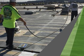 A worker in a neon green t-shirt applies an elastomeric roof coating to a mod bit roof using a spray gun.